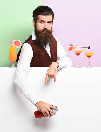 handsome bearded barman with long beard and mustache has stylish hair on serious face holding shaker and made alcoholic cocktail in vintage suede leather waistcoat on purple green studio background Stock Photo