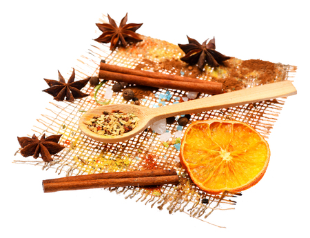 spiciness: set of ingredients for cooking spicy fragrant spices in spoons with cinnamon, star anise lies and orange on sackcloth isolated on white background, side view