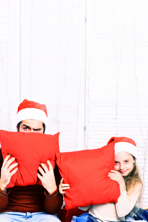 red pillows: handsome bearded man with long beard in christmas hat and cute blonde smiling girl with blue checkered plaid hiding behind red pillows on white studio background, copy space Stock Photo