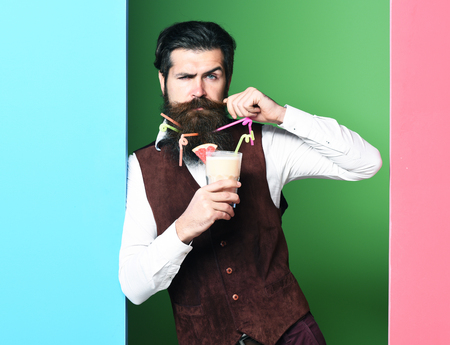 handsome bearded man with long beard and mustache has stylish hair on serious face holding glass of alcoholic beverage in vintage suede leather waistcoat on blue green studio background, copy space