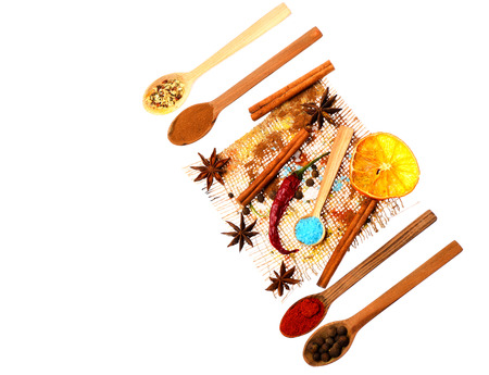 spiciness: set of ingredients for cooking spicy fragrant spices in spoons with coriander and pepper, chili pepper, paprika, cinnamon and orange lies on sackcloth isolated on white background, copy space