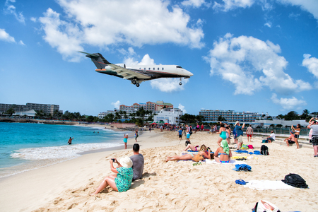 St Maarten, Kingdom of Netherlands - February 13, 2016: beach crowds observe low flying airplanes landing near Maho Beach on island of St Maarten in the Caribbean Editorial