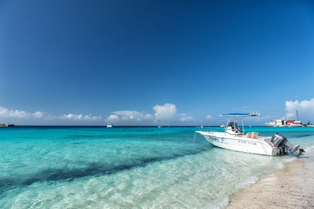 Grand Turk, Turks and Caicos Islands - December 29, 2015: motor boat on sandy beach sunny outdoor. big cargo ship red color with crane and many containers on ocean water and blue cloudy sky background Editorial