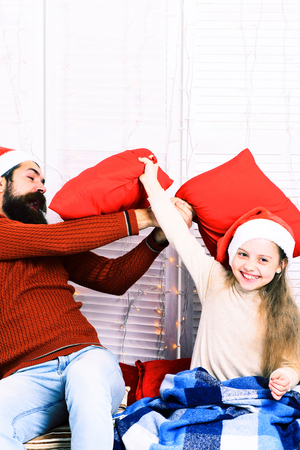 red pillows: handsome bearded funny man with long beard in christmas hat and cute blonde smiling girl with blue checkered plaid fight with red pillows on white studio background