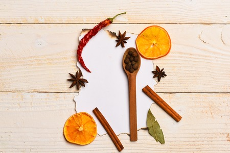 spiciness: set of ingredients for cooking spicy fragrant spices with dried orange and pepper, allspice, cinnamon, chili pepper lie on white paper for notes on vintage wooden background, copy space Stock Photo