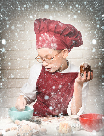 young boy cute cook chef in red uniform and hat on stained face with glasses sitting on table with colorful bowls, tasty cookies, rolling pin and holding chocolate cake on white brick wall background