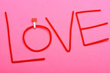 hilo rojo: Love word from red thread for Valentines day with clothespin on pink background Foto de archivo