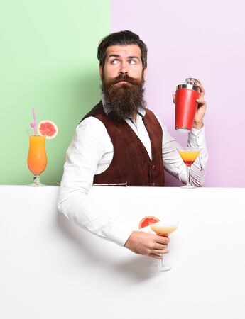 handsome bearded barman with long beard and mustache has stylish hair on surprised face holding shaker and made alcoholic cocktail in vintage suede leather waistcoat on purple green studio background