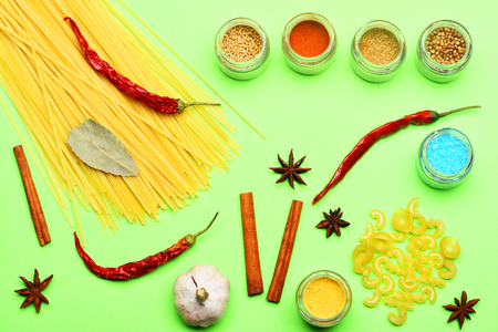 spiciness: set of colorful spices with garlic, salt, cinnamon, pasta, jars, curry, paprika, turmeric, chili pepper, star anise on green background, top view Stock Photo