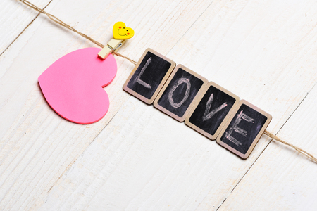 yellow clothespin with smiling emotion holding pink valentine card and black boards with word Love on clothesline on white vintage wooden background, copy space