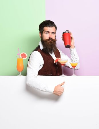 handsome bearded barman with long beard and mustache has stylish hair on serious face holding shaker and made alcoholic cocktail in vintage suede leather waistcoat on purple green studio background Stockfoto
