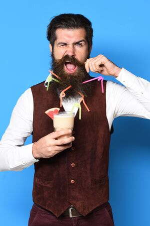 handsome bearded man with colorful tubes in long beard and mustache has stylish hair on funny face holding glass of alcoholic cocktail in vintage suede leather waistcoat on blue studio background Stock Photo
