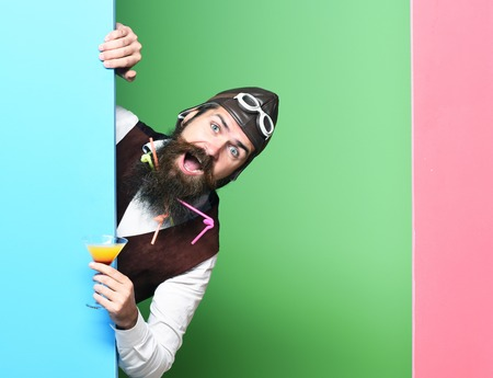 handsome bearded pilot or aviator man with long beard and mustache on smiling face holding glass of alcoholic beverage in vintage suede leather waistcoat with hat and glasses on studio background Stock Photo