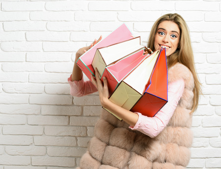 young fashionable sexy pretty woman or girl with long beautiful blonde hair in waist coat of beige fur and fashion makeup holding colorful package on brick wall studio background Stock Photo