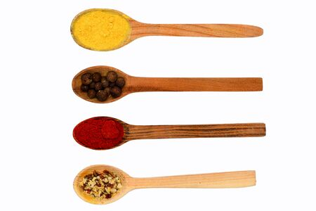 spiciness: spicy fragrant paprika, allspice, turmeric in wooden spoon isolated on white background, top view