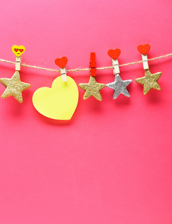 yellow valentine heard or card with silver and golden stars hanging on clothesline on red background, copy space Stock Photo