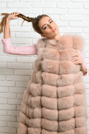cola mujer: young fashionable sexy pretty woman or girl in waist coat of beige fur and fashion makeup holding beautiful long blonde hair in tail on brick wall studio background Foto de archivo