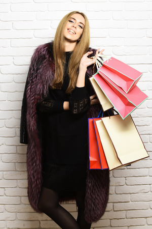 fashionable sexy pretty woman or girl with beautiful blonde hair in waist coat of burgundy fur with black dress and fashion makeup holding many colorful package on white brick wall studio background Stock Photo