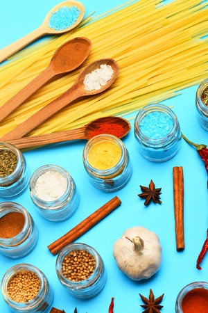 spiciness: set of colorful spices with spoons, garlic, salt, cinnamon, pasta, jars, curry, paprika, turmeric, chili pepper, star anise on blue background, side view