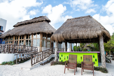 a house with a straw: exotic beach bar with house building and straw roof near chairs on sand outdoor on blue cloudy sky background