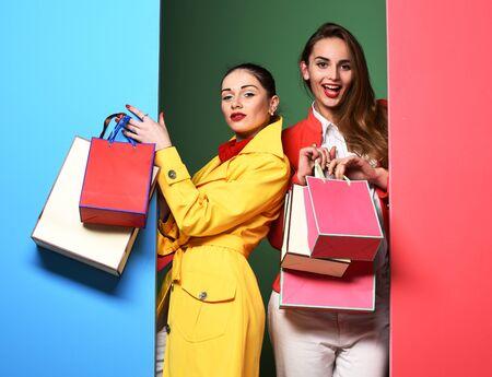 jóvenes atractivo bastante divertidos mujeres o modelo niñas con el pelo largo hermoso en la cara feliz en batas de color rojo y amarillo colorido con el maquillaje de moda la celebración de bolsas en el estudio de fondo azul verde