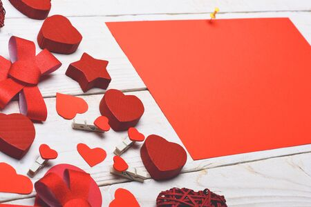red sheet: set of colorful decorative valentine hearts, cute bow, pegs and red sheet paper on white vintage wooden background, copy space
