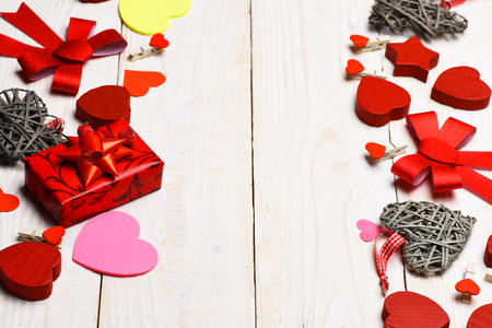set of colorful decorative valentine hearts with checkered ribbon, red present or gift and cute bows on white vintage wooden background, copy space Stock Photo