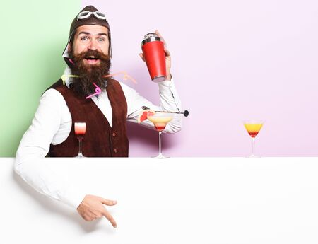 handsome bearded aviator or pilot with long beard and mustache on smiling face with shaker alcoholic cocktail in vintage suede leather waistcoat with hand and glasses on purple green studio background