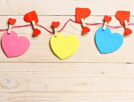 set of colorful valentine hearts hanging with clothespin on clothesline on white vintage wooden background, copy space