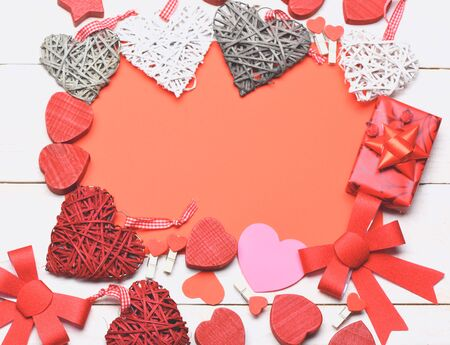 red sheet: set of colorful decorative valentine hearts with checkered ribbon, cute bows, present, pegs and red sheet paper on white vintage wooden background, copy space