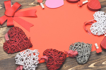 red sheet: set of colorful decorative valentine hearts with checkered ribbon, cute bow, pegs and red sheet paper on brown vintage wooden background, copy space