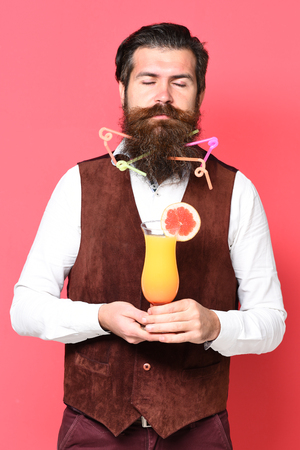 handsome bearded man with colorful tubes in long beard and mustache has stylish hair on serious face holding glass of alcoholic cocktail in vintage suede leather waistcoat on red studio background Stock Photo
