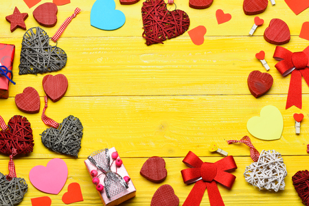 set of colorful decorative valentine hearts with checkered ribbon, pegs or clothespins and cute present in circle on yellow vintage wooden background, copy space Stock Photo