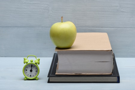 12 oclock: Books, fresh green apple and alarm clock on vintage wooden background, education concept Stock Photo