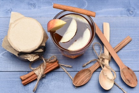 string top: Set of glass of apple juice with different types of nuts in glass jar covered craft paper, cinnamon with string and spoons on blue vintage wooden background, top view Stock Photo