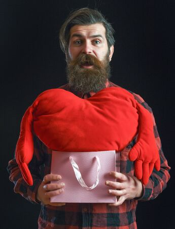ag: handsome bearded man or guy in checkered shirt with fashionable mustache and beard on surprised face holds valentines red heart pillow in pink shopping bag or package on black background