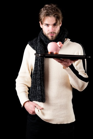 handsome bearded man or guy with beard on face in white sweater and knitted on black background holds laptop and pink piggy moneybox
