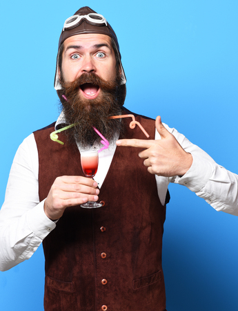 handsome bearded pilot or aviator man with long beard and mustache on surprised face holding glass of alcoholic shot in vintage suede leather waistcoat with hat and glasses on blue studio background