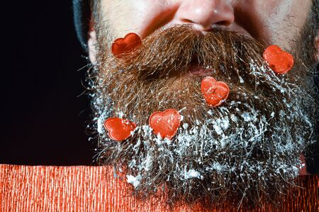 boca cerrada: handsome bearded man or guy with fashionable mustache, has closed mouth on face and red decorated hearts with snow in beard near paper on black background, copy space