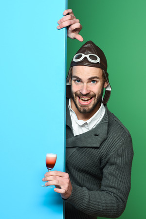 handsome bearded aviator man with long beard on funny face holding glass of alcoholic shot in gray knitted sweater with hat and glasses on blue green studio background Stock Photo