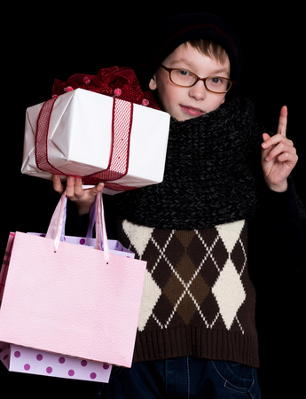 finger bow: small smiling boy or cute nerd kid in glasses, hat and fashionable knitted scarf on black background holds white present box with red bow and shopping bags, holds raised finger