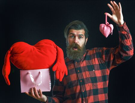 ag: handsome bearded man or guy in checkered shirt with fashionable mustache and beard on surprised face holds valentines red heart pillow and pink shopping bag or package on black background