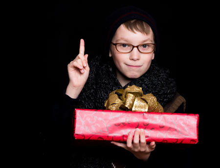 finger bow: small smiling boy or cute nerd kid in glasses, hat and fashionable knitted scarf on black background holds red present box with golden bow and raised finger Stock Photo