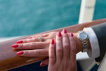 Mani femminili e orologio da polso con il manicure rosso e anello d'oro al dito con diamanti in prossimità di acqua Archivio Fotografico - 69875916