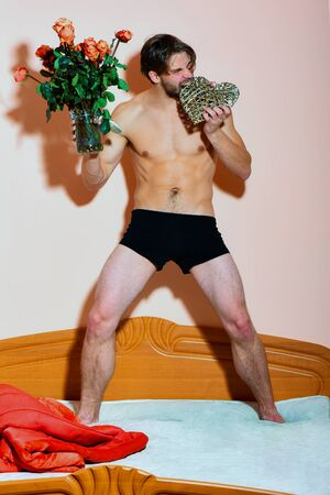 nackte brust: handsome bearded sexy macho man with stylish beard standing in underwear on bed near red blanket holding orange roses and bites decorative valentine heart with muscle torso on athletic body