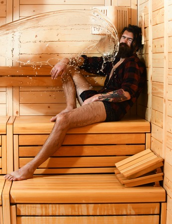 bather: Handsome man or bather, bearded hipster with beard and moustache in red checkered shirt wet with big splash of water in sauna, thermal bath on wooden background Stock Photo