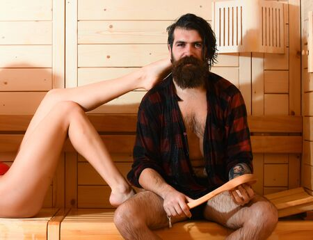 bather: Handsome man or bather, bearded hipster with beard and moustache in red checkered shirt and sexy female legs wet of water in sauna, thermal bath on wooden background