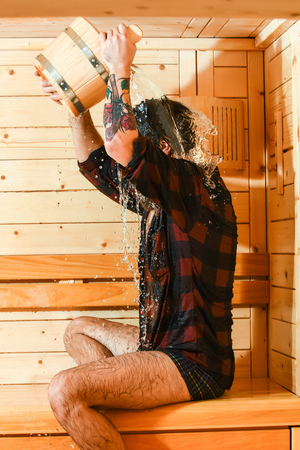 bather: Handsome man or bather, bearded hipster with beard and moustache in red checkered shirt pours water from bucket on head in sauna, thermal bath on wooden background Stock Photo