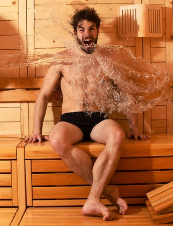 bather: Excited man or bather with muscular sexy torso, body, wet with big splash of water in sauna, thermal bath on wooden background
