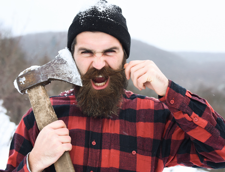 Angry man or brutal lumberjack, bearded hipster, with beard and moustache in red checkered shirt shaves with axe blade in snowy forest on winter day outdoors on natural background Foto de archivo